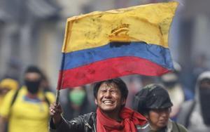 Un manifestante muestra la bandera de Ecuador en medio de una protesta.