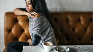 Una chica toma un café sentada en el sofá.
