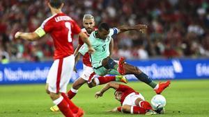 El valencianistaNani cae entre tres jugadores suizos.
