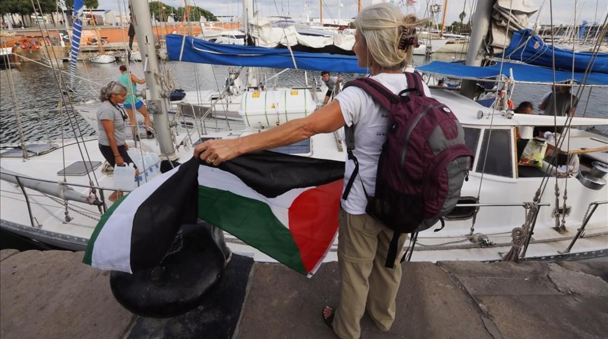 Una activista con la bandera palestina frente a uno de los dos veleros de la flotillaque ha partido hacia Gaza.