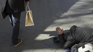 Una personapide limosna en el Paseo de Gràciade Barcelona.
