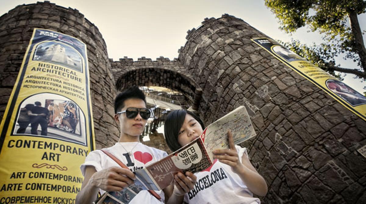 Una pareja de turistas, en la puerta del Poble Espanyol.