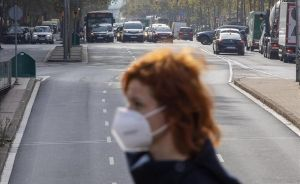 Una mujer con mascarilla pasa frente a los coches en la Gran Via de Barcelona.