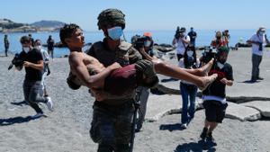 Un soldado español carga con un adolescente en Ceuta.
