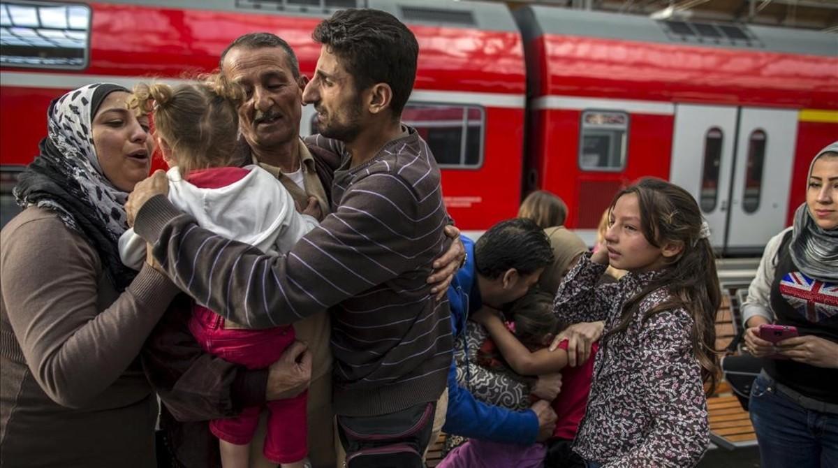 Un refugiado sirio se une a su familia tras llegar a la estación deLubeck en Alemania en septiembre del 2015.