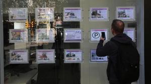 Un hombre mira la ofertade pisos en una inmobiliaria de Barcelona.