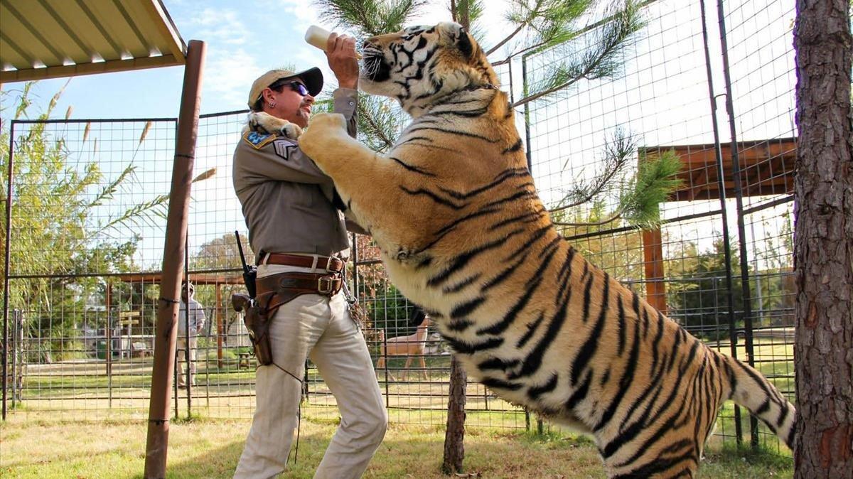Joe Exotic, revólver al cinto, con uno de sus tigres.