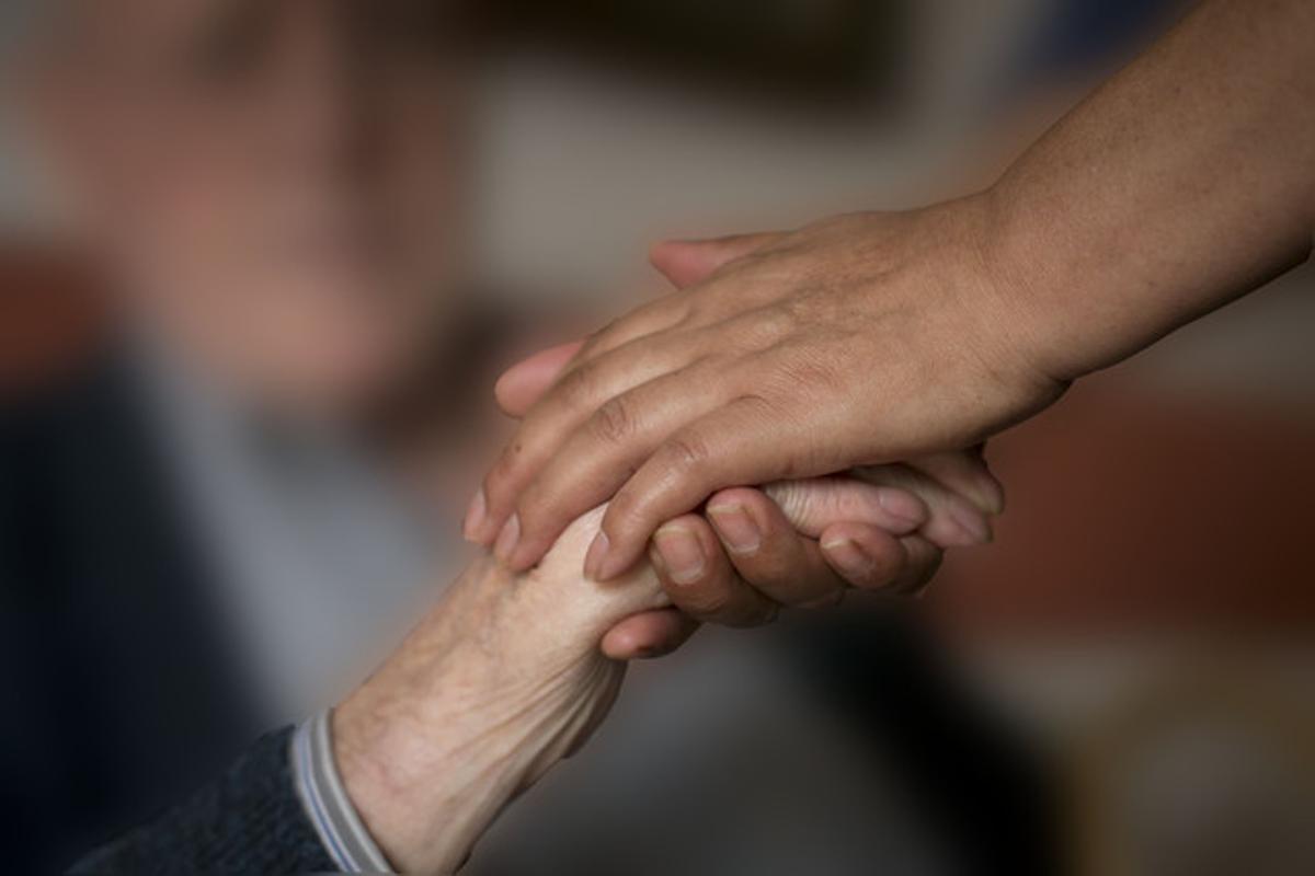 Un hombre le sostiene la mano a un enfermo