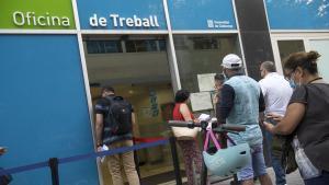 Personas haciendo cola frente a las oficinas públicas de empleo, en Barcelona.