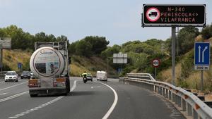Un camión circula por la N-340 ante un panel que advierte de la prohibición, cerca de Altafulla.