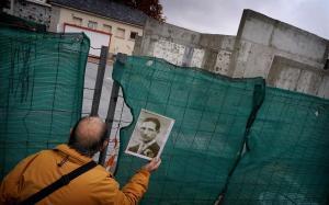 Tomás Montero, hijo del ugetista fusilado en 1939 Tomás Montero Labrandero, se asoma por un hueco de la verja para ver cómo arrancan las placas que homenajeaban a su padre y otros 2.937 republicanos en el cementerio madrileño de La Almudena.