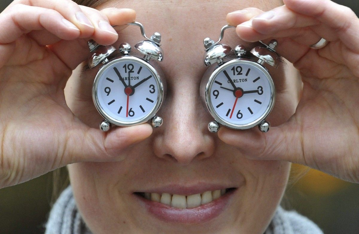 Una mujer muestra dos relojes con el cambio de hora, en una foto de archivo.