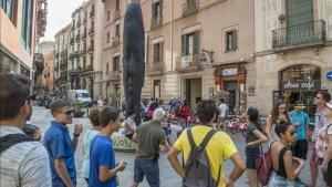 Un grupo de turistas junto a 'Carmela', la escultura de Plensa que hay frente al Palau de la Música.