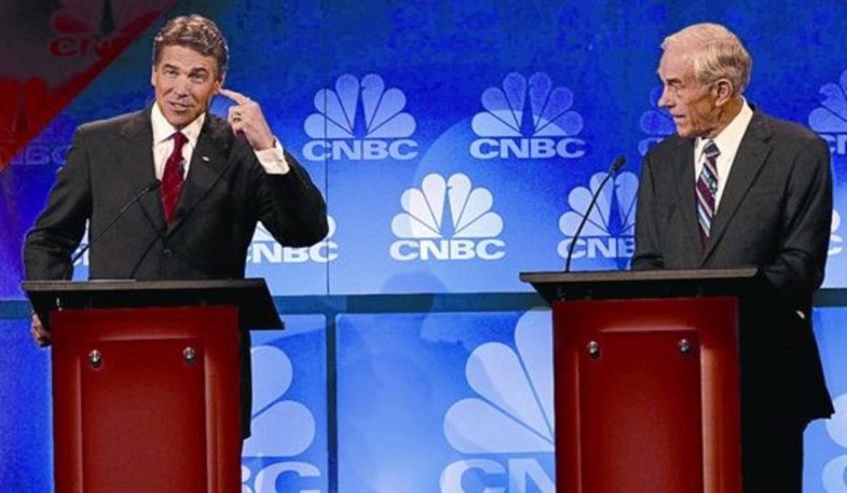 El candidato republicano Rick Perry mira sus notas durante un debate en la Universidad de Oakland.