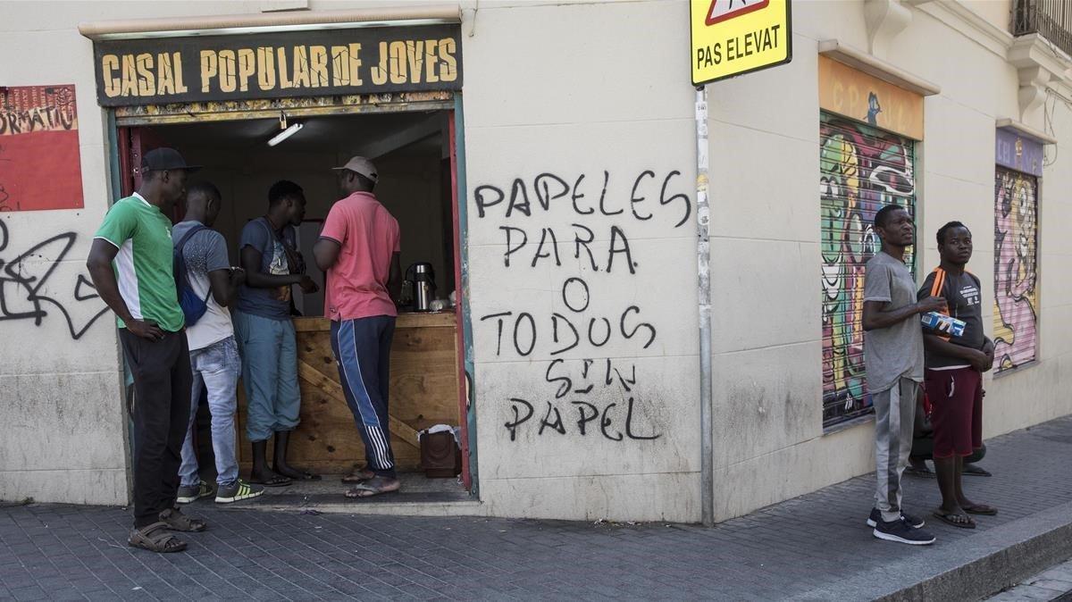 Varios voluntarios se ofrecen ante el Casal de joves de Lleida para dar de comer a los migrantes sin trabajo.