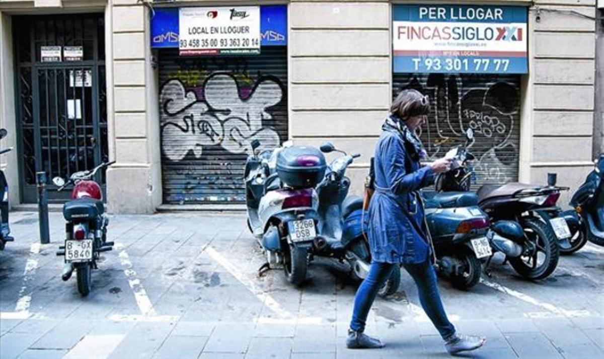 Locales comerciales cerrados en la calle de Sant Pere més Alt, en Ciutat Vella.