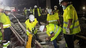 Unos operarios trabajan en la nueva configuración del esquema de vías de ancho convencional en la estación de Sants.