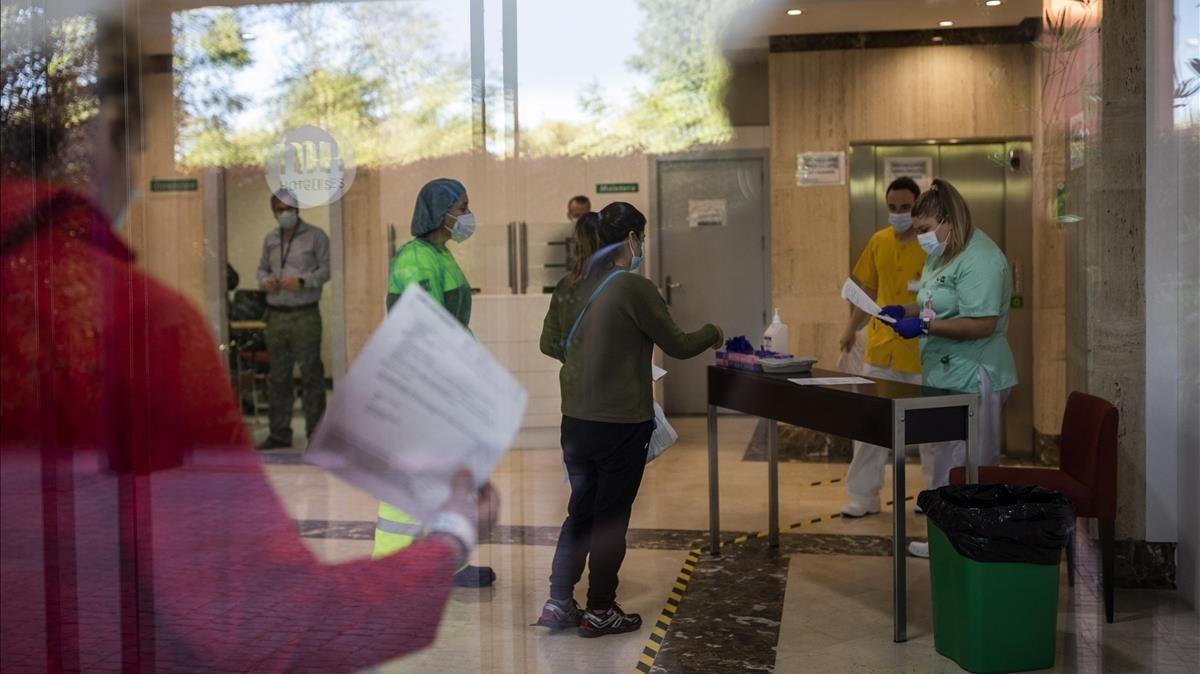 Una enfermera (derecha) recibe a una paciente con covid-19 en un hotel en Leganés para que pase la cuarentena, este jueves.