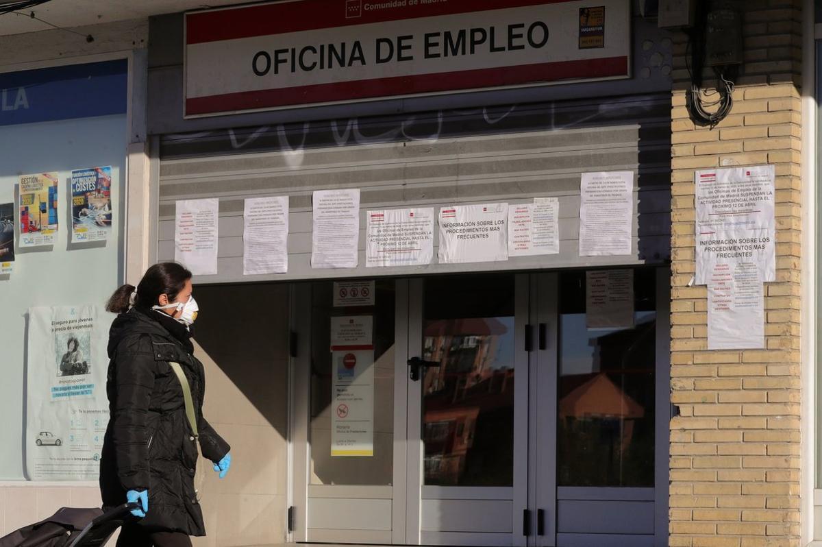 Una mujer pasa ante una oficina de empleo.