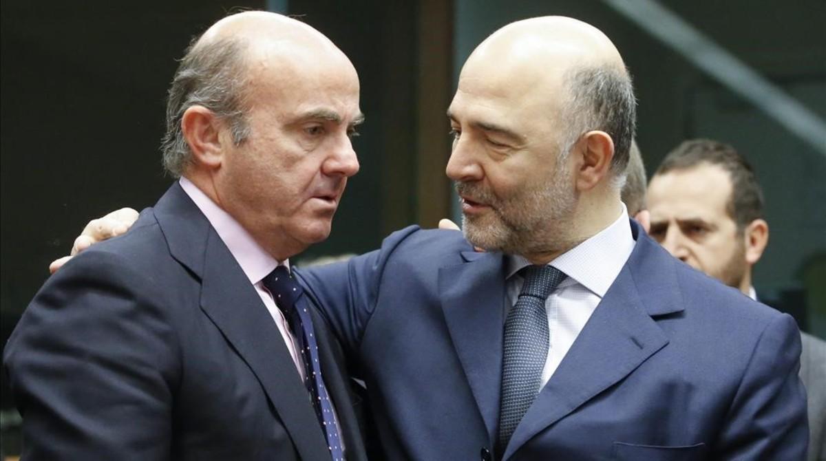 El ministro español de Economía, Luis de Guindos, conversa con el comisario europeo de Asuntos Economicos, Pierre Moscovici.