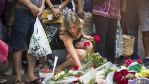 Una joven deposita una ramo de flores en el mosaico de Miró. JORDI COTRINA