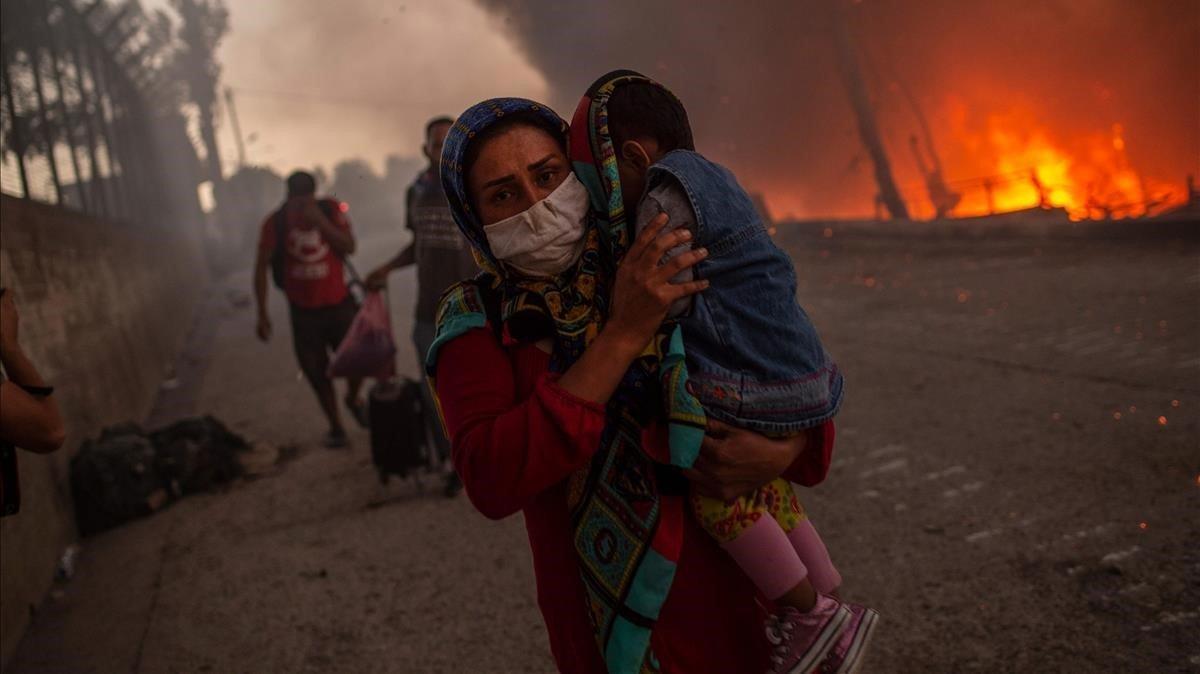 Una madre huyo con su hijos de las llamas en el campo de refugiados de Moria, en Lesbos.