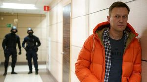 (FILES) In this file photo taken on December 26  2019 Russian opposition leader Alexei Navalny stands near law enforcement agents in a hallway of a business centre  which houses the office of his Anti-Corruption Foundation (FBK)  in Moscow  - Russian opposition leader Alexei Navalny said on December 21  2020 he had tricked a security agent into admitting the Federal Security Service (FSB) sought to kill him this summer and placed poison in his underwear  (Photo by Dimitar DILKOFF   AFP)