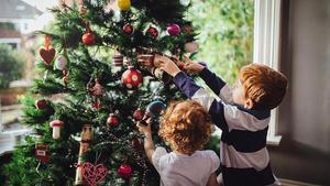 Unos niños decoran el árbol de Navidad.