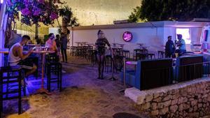 Varias personas apuran los minutos antes del cierre de un bar en Ibiza.