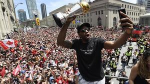 Kawhi Leonard se hace un selfie con el trofeo de campeón de la NBA.