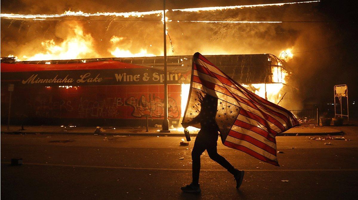 Un manifestante porta una bandera estadounidense al revés, junto a un edificio en llamas, en Minneápolis eljueves 28 de mayo.
