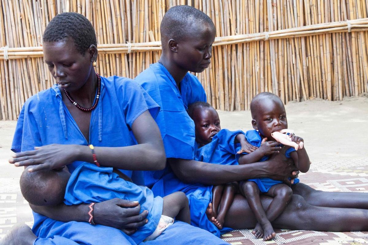 Dos mujeres cuidan a sus hijos malnutridos en un centro de estabilización de Sudán del Sur.