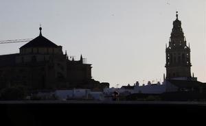 Una mujer protegida con mascarilla camina por uno de los puentes de Córdoba, en las inmediaciones de la mezquita