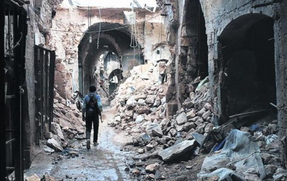 Un miliciano camina por entre las ruinas que han dejado los bombardeos en el zoco antiguo de Alepo, una ciudad habitada desde hace 7.000 años.