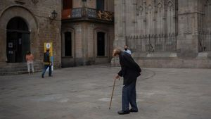 Un hombre mayor camina por una plaza del barrio Gòtic de Barcelona.