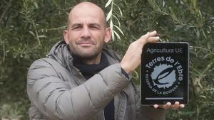 Toni Morelló muestra la etiqueta de su aceite con el sello Reserva de la Biosfera.