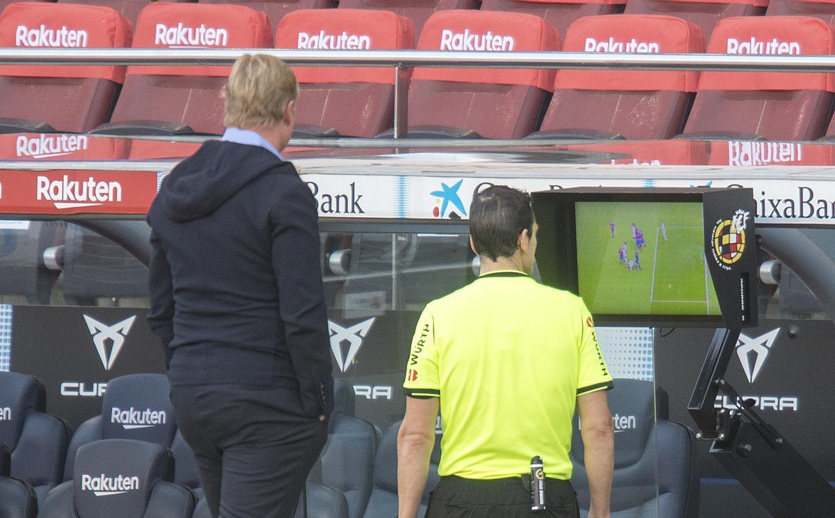 Koeman observa como Martínez Munuera visiona el penalti de Lenglet a Ramos en el clásico.