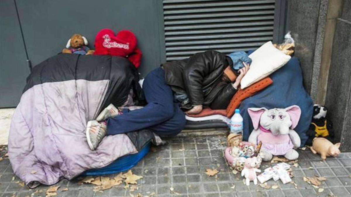 Tres tan ricos como 14 millones de españoles. En la imagenun sin techo en paseo de Sant Joan.