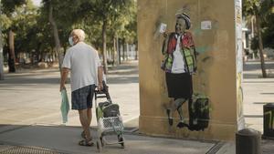 Un hombre pasa delante del dibujo de TVboy del rey emérito Juan Carlos I en el parque de la Barceloneta, este jueves.