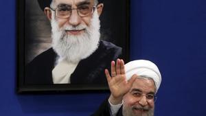 El presidente iraní,HasánRohaní, saluda frente a una foto del guía supremo, el ayatola Alí Jamenei.