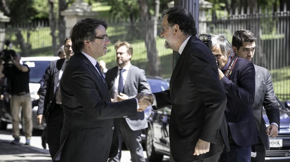 Carles Puigdemont y Mariano Rajoy se saludan este viernes, en Barcelona, antes de la inauguración del Salón de Automóvil de Barcelona.