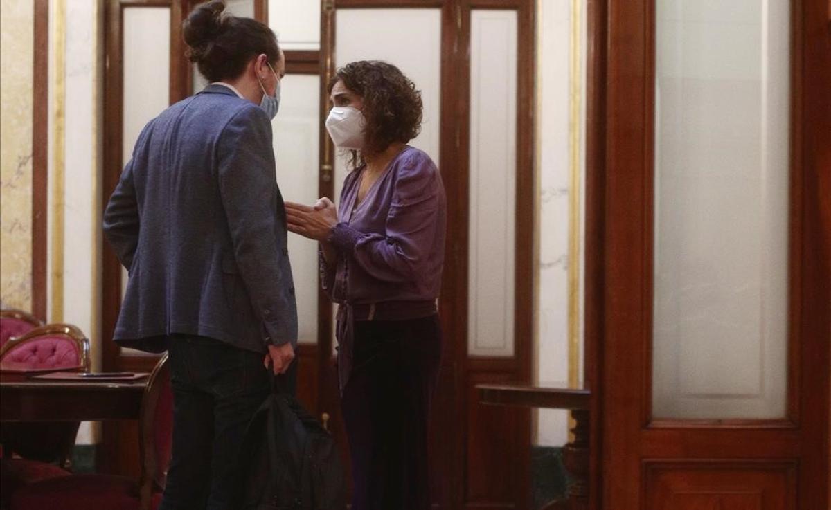 El vicepresidente del Gobierno, Pablo Iglesias, y la portavoz y ministra de Hacienda, María Jesús Montero, discuten en los pasillos del Congreso.