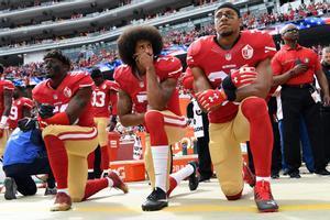 Colin Kaepernick, de rodillas mientras suena el himno de EEUU.