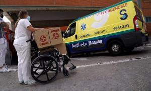 Una sanitaria carga material en una silla de ruedas a las puertas del servicio de Urgencias del Hospital Virgen de la Salud de Toledo.