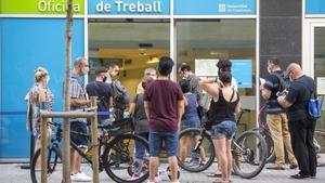 Un grupo de personas delante de una oficina del SEPE en Barcelona.