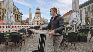 Alemania registra un máximo diario de 410 muertos por coronavirus. En la foto, un camarero ordena las mesas de su bar, en Berlín.