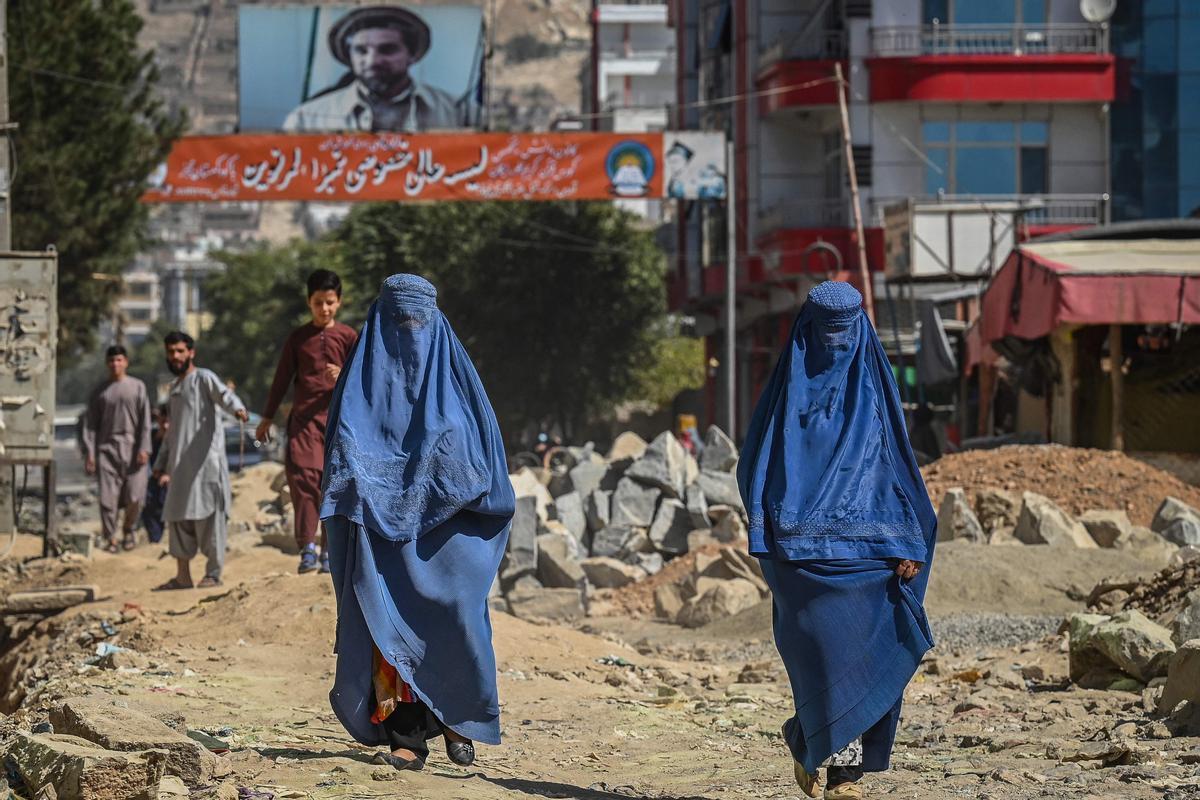 Dos mujeres con burka caminan por una calle con escombros en Kabul.