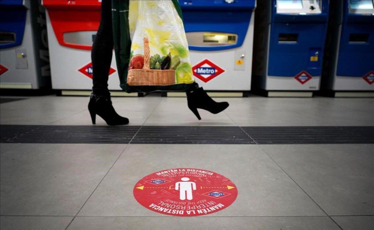 Una pegatina en el suelo en el metro de Madrid invita a mantener la distancia social por el coronavirus.