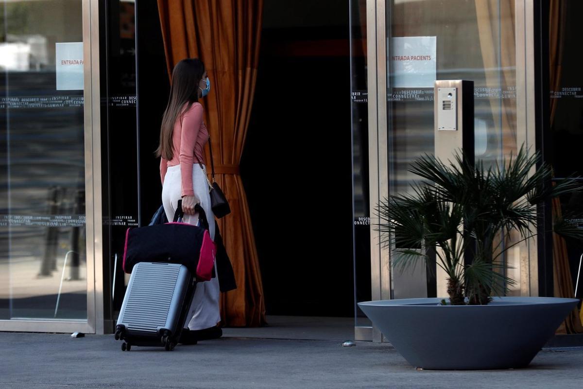GRAFCAT4397. BARCELONA, 06/04/2020.- Una mujer entra en el hotel Renaissance Fira, habilitado como lugar de aislamiento para enfermos leves de Covid-19, este lunes, vigesimotercer día de confinamiento por el estado de alerta declarado por el Gobierno por la pandemia de coronavirus. EFE/Toni Albir