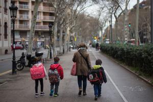 Imagen de archivo de una madre llevando a sus hijos al colegio